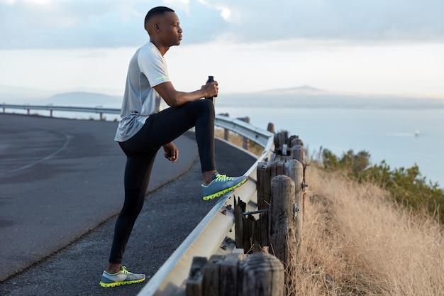 L'immagine di un uomo motivato nero tiene una bottiglia di bevanda fresca, vestito con una tuta da ginnastica, concentrato in lontananza, ammira la bellissima natura, gode dell'aria fresca, fa jogging intensivo all'aperto da solo