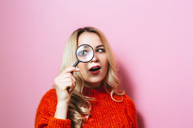 The image of a blonde girl dressed in a red sweater and holding a magnifying glass on a pink wall