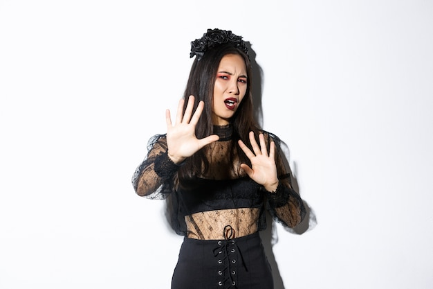 Immagine di donna asiatica infastidita e infastidita in elegante abito gotico alzando le mani sulla difensiva, facendo smorfie dalla carne della fotocamera, chiedendo di smettere di scattare foto di lei, in piedi sfondo bianco.