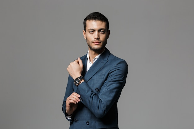 Image of brunette arabic businessman 30s in formal suit and demonstrating wristwatch, isolated over gray wall