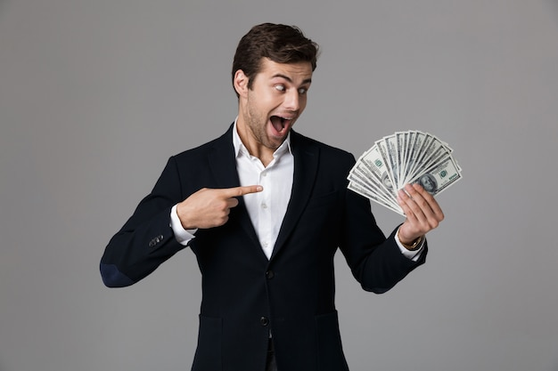Image of brunette businessman 30s in suit smiling and holding fan of money in dollar banknotes, isolated over gray wall