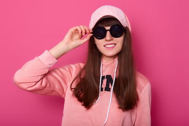 Image of brunette cool girl wears pink hoodie and cap.