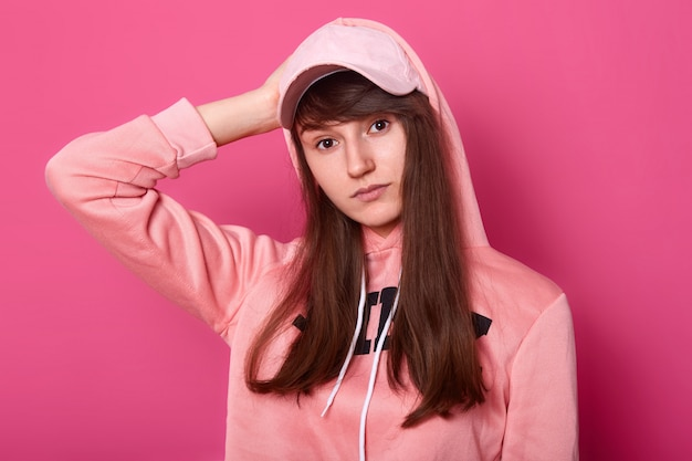 Image of brunette girl looks at camera with serious and thoughtfull facial expression, wearing casual pink hoody and cap isolated on rose
