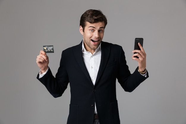 Image of brunette man 30s in business suit holding black mobile phone and credit card, isolated over gray wall