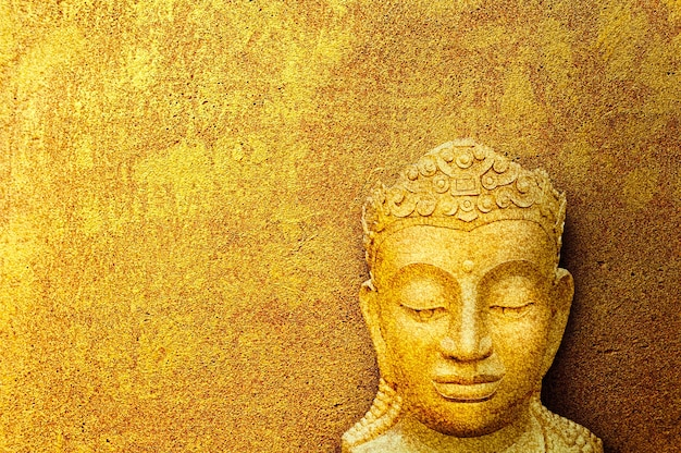 Image of buddha face, concept of buddha image on golden grunge cement background.