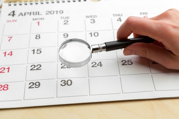 Image of business and meetings. calendar to remind you an important appointment and magnifying glass