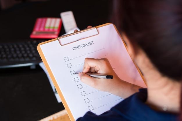 Image of businessfemale preparing checklist at office desk