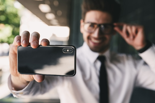 Image of businesslike man dressed in formal suit standing outside glass building, and taking selfie photo on smartphone