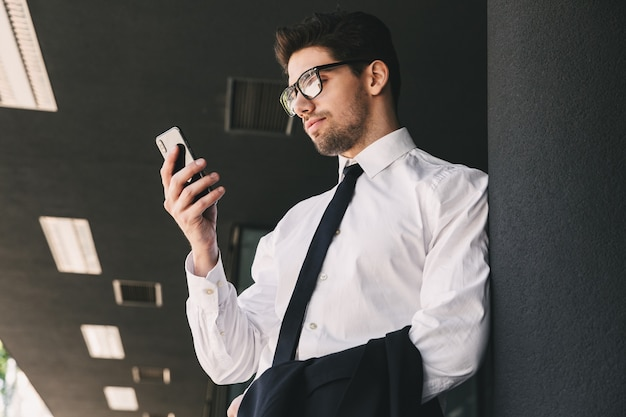 Image of businesslike man dressed in formal suit standing outside glass building, and using smartphone