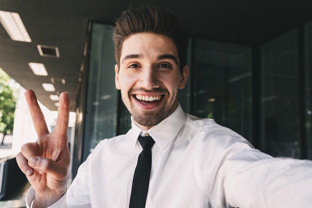 Image of businessman dressed in formal suit standing outside glass building, and taking selfie photo