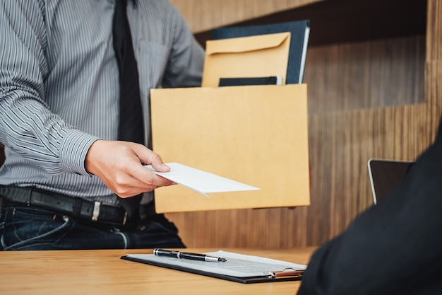 Image of businessman hand holding cardboard box and sending a resignation letter
