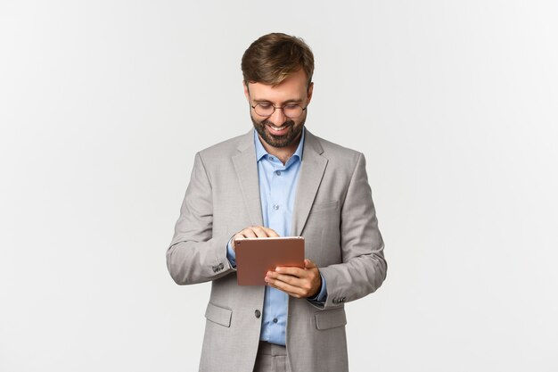Image of businessman working looking at digital tablet and smiling pleased standing in grey suit and...