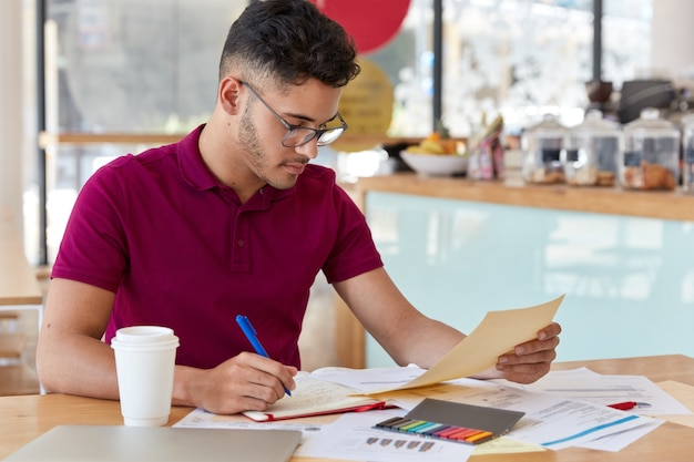 Image of busy unshaven copy writer or college student dressed in casual clothing, makes notes in notebook, focused into document, looks attentively, poses at small cafetiera, drinks hot beverage.