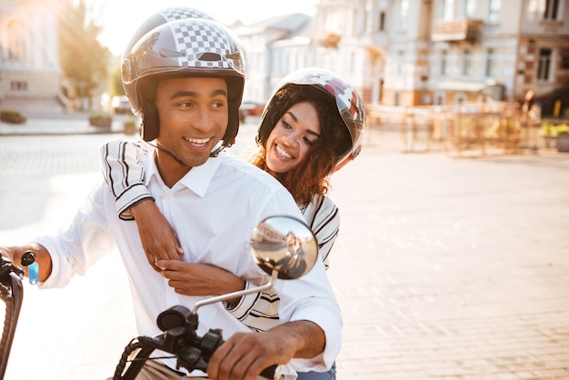 Image of carefree african couple rides on modern motorbike on the street