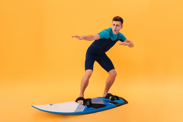 Image of a carefree surfer in wetsuit using surfboard like on wave