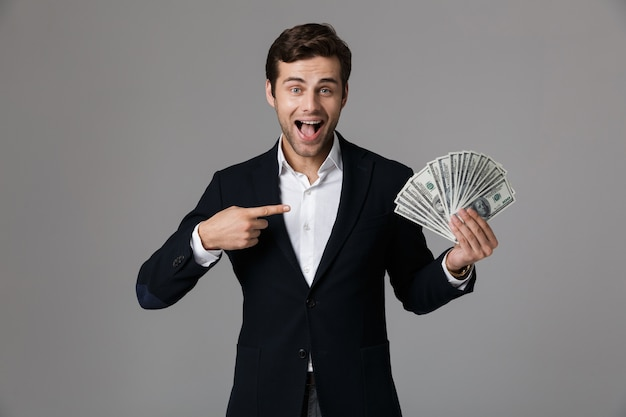Image of caucasian businessman 30s in suit smiling and holding fan of money in dollar banknotes, isolated over gray wall