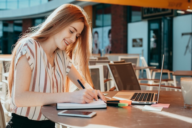The image of a caucasian businesswoman with red hair and freckles working on some documents outside at the computer