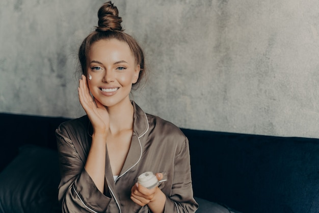 Image of caucasian cheerful woman in silk pajama smiling while gently applying moisturizing face cream isolated over concrete wall background in bedroom. beauty and skincare concept