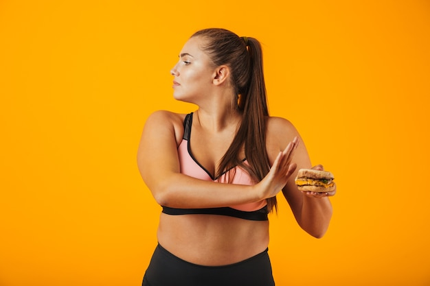 Image of caucasian chubby woman in tracksuit doing stop gesture while holding sandwich, isolated over yellow background