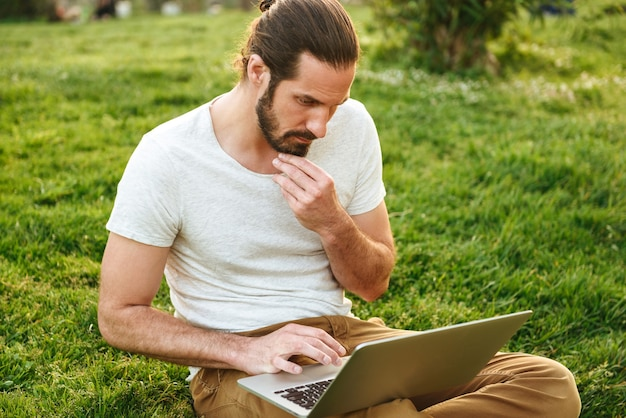 Image of caucasian concentrated man in casual wear sitting on grass in green park and working on silver laptop
