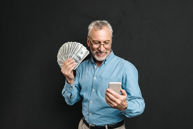 Image of caucasian elderly man 70s with gray hair holding mobile phone and lots of money dollar currency, isolated over black wall