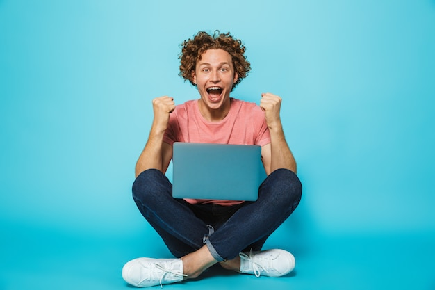 Image of caucasian happy man with brown curly hair rejoicing and clenching fists, while sitting on floor with legs crossed