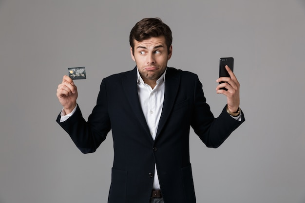 Image of caucasian man 30s in business suit holding black cell phone and credit card, isolated over gray wall