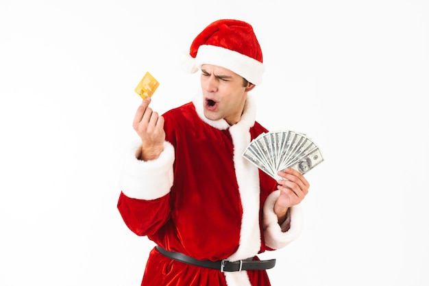 Image of caucasian man 30s in santa claus costume holding dollar bills and credit card