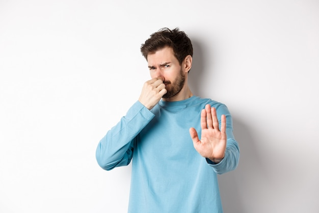Image of caucasian man stretch out hands to stop or reject something, shut nose disgust, refusing product with bad smell, standing over white background