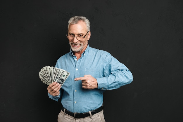 Image of caucasian middle aged man 60s with gray hair pointing finger on money prize holding lots of dollar banknotes, isolated over black wall
