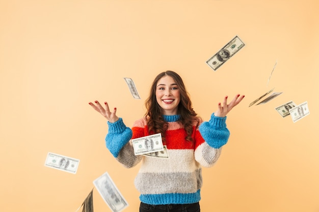 Image of caucasian woman 20s with long hair smiling and standing under falling money, isolated