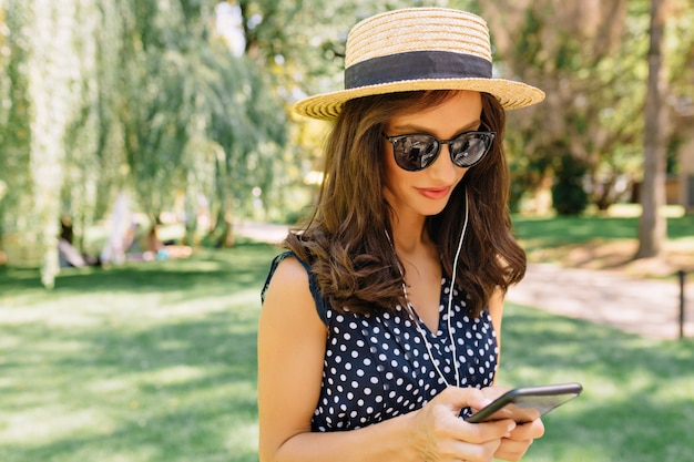 Image of charming style woman is walking in the summer park wearing summer hat and black sunglasses and cute dress.