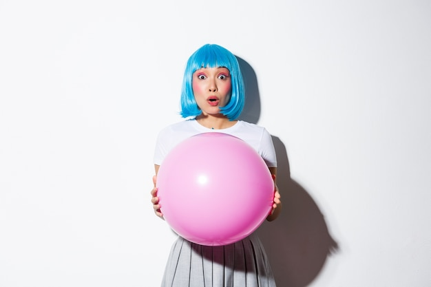 Image of cheerful asian girl in blue wig, celebrating holiday, wearing outfit for halloween party