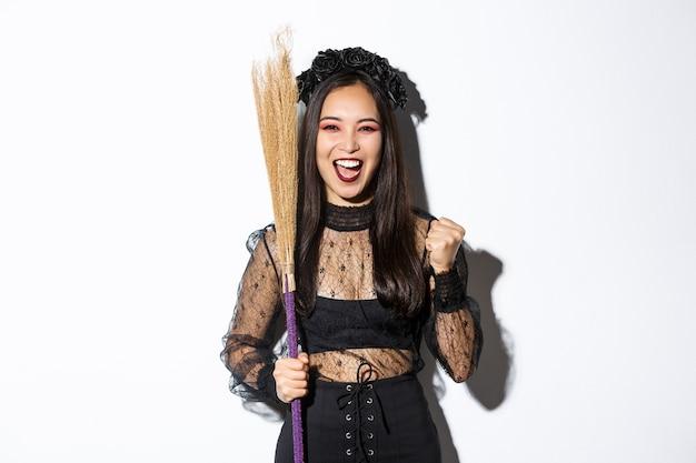 Immagine della ragazza asiatica allegra in costume da strega che celebra la vittoria, tenendo la scopa, dicendo di sì e alzando il pugno in trionfo, sfondo bianco.