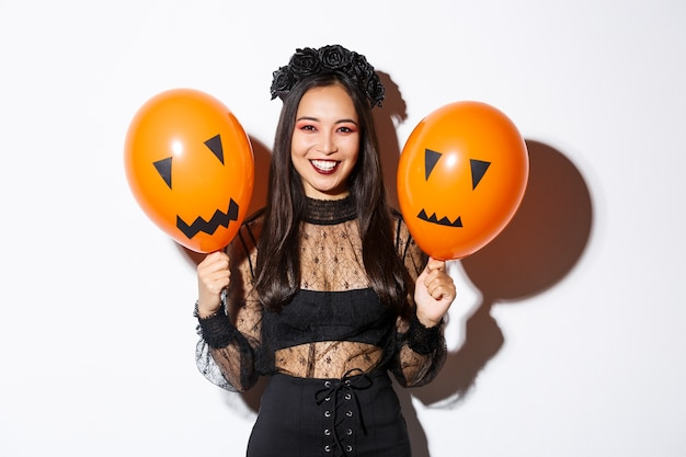 Image of cheerful asian woman in witch costume celebrating halloween, holding balloons with scary faces, standing over white background.