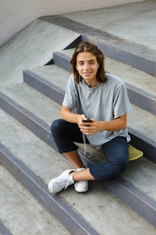 Image of cheerful attractive young skater guy sit in the park listening music with earphones using phone.