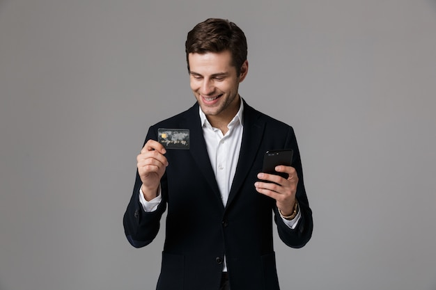 Image of cheerful businessman 30s in suit holding credit card and smartphone, isolated over gray wall