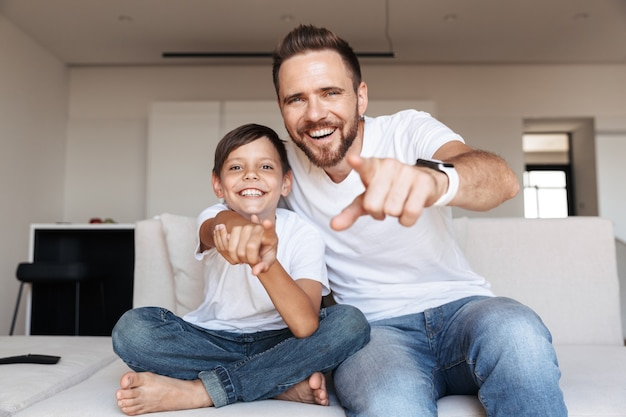 Image of cheerful glad father and son laughing, while pointing finger at you and sitting on sofa in apartment