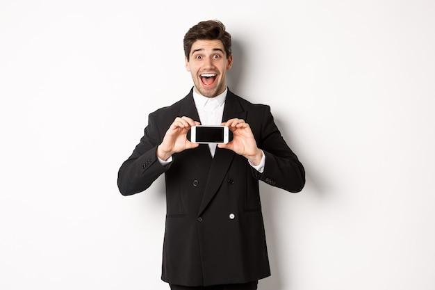 Immagine di un uomo allegro e bello in abito nero, che mostra lo schermo di smarthone e sembra stupito, in piedi su sfondo bianco