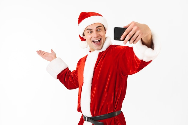 Image of cheerful man 30s in santa claus costume holding smartphone and taking selfie