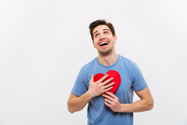 Image of cheerful man in t-shirt hugging paper heart
