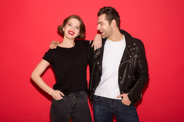 Image of cheerful punk couple hugging and posing together over red wall
