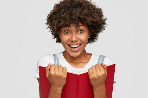 L'immagine della donna sorridente allegra impara il materiale dal libro
