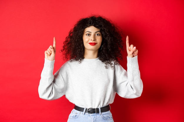 Image of cheerful smiling woman with curly hairstyle and red lips, pointing fingers up at empty space, showing advertisement, standing in casual clothes on studio background.