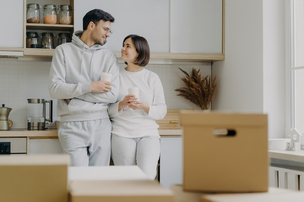 Image of cheerful woman and man have pleasant talk during coffee break, wear casual clothes, move in new apartment, pose with modern furnished kitchen, unpack cardboard boxes with household stuff