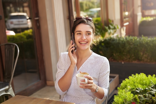 Image of cheerful young brunette woman with cup of coffee in raised hand having phone conversation and smiling joyfully, sitting at table over city cafe interior