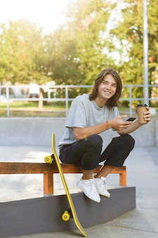 Image of cheerful young skater guy sit in the park with skateboard using mobile phone drinking coffee.