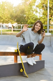 Image of cheerful young skater guy sit in the park with skateboard using mobile phone waving.