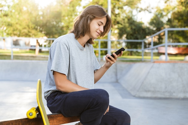 Image of cheerful young skater guy sit in the park with skateboard using mobile phone.