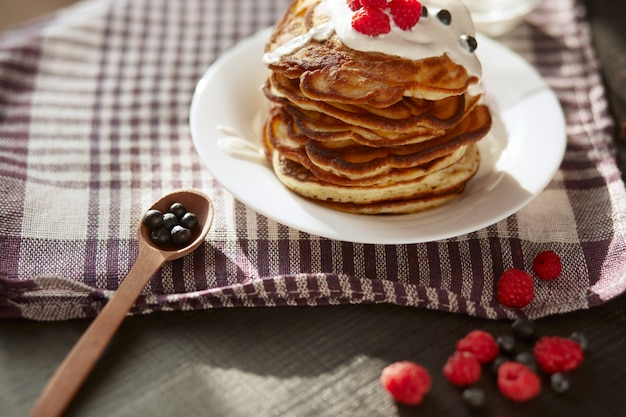 Image of cheese pancakes with sour cream and fresh berries, blackberry jam in wooden spoon, whipped cream on muffins top